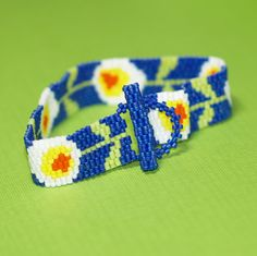 Darling Daisy Chain...  Remember making daisy chains when you were little?  This narrow little peyote bracelet will take you back to your idyllic childhood days, with its pretty stylized daisies that run from end to end.  :-)  from time2cre8, $ 31