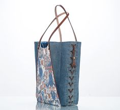 This Eco Fashion bag is one-of-a-kind; built to carry a large and heavy load. Materials: Upcycled ikat denim jeans and lace-up-the-side vintage denim blue jeans. Measures: 15.5high. 18w at the top with a 5w bottom Handcrafted leather strap handle 11.5 drop Inside: Denim lining One