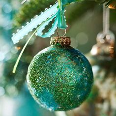 Coat an ornament with spray adhesive. Sprinkle a mixture of 2 colors of glitter on the ornament or roll it in glitter, covering the ornament entirely. Once dry, tie two coordinating colors of ribbon in a bow around the ornament hanger.
