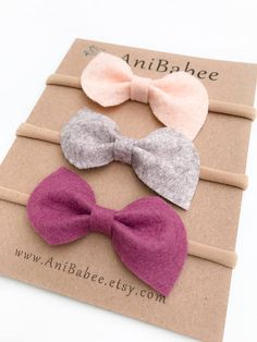 Felt Bow Headband Set in Wheat Fields, Driftwood and Mulberry. Pictured in the DAINTY & MIA bow styles. Felt Bows Measure approximately 2 x .75 and are attached to a 1/8 ivory skinny elastic band. **Listing is for 3 Headbands** Please remember to select the appropriate size! The sizes below