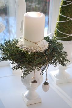 A candle all dressed up for Christmas. Just take away the greenery and added beads and you have a year round decoration. White goes with eveything