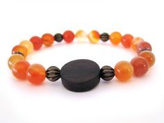 Bright and cheery 8mm carnelian beaded stretch bracelet will add the perfect pop of color to any spring and summer outfit. The focal bead is made from ebony wood. Wear this handmade bracelet as a statement piece or layer with other Rock & Hardware bracelets for an entire arm party! Rock & Hardware Jewelry