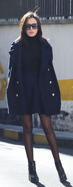 Lucita Yañez is wearing a black and blue outfit, skirt, top and boots from Zara and the coat is from H&M