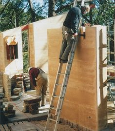 A photo of two workers erecting a rammed earth wall.