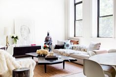 A bright living space complete with neutral tones in the sofa and fur throws, a black coffee table, and a decorative metal lantern.