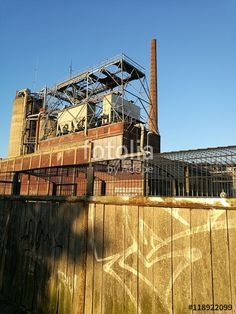 Holzzaun mit Graffiti an einer alten Fabrik mit Schornstein am Hafen in Münster in Westfalen im Münsterland