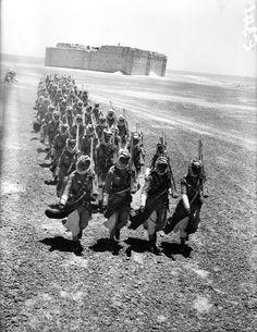 Soldados de la Legión Arabe jordana marchan cerca de la fortaleza de Qasr al-Hara. Están armados con fusiles británicos Lee-Enfield de 7,7 mm. (1941)