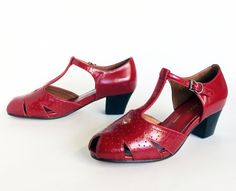 A 1920's / 1930's style T-Strap in perforated patent leather, featuring a stacked leather heel. Patent leather uppers with leather soles. (Gabrielle)
