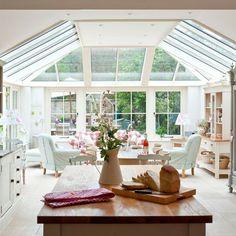 Land Wintergarten mit offenem Schnitt. Diese offene Wohnküche Wintergarten, in natürlichem Licht durch die vom Boden bis zur Decke reichenden Fenster gebadet. Der karierte Stuhl Abdeckungen einen englischen Land fühlen.