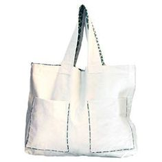 """Canvas beach bag with patterned interior lining and 2 front pockets. Crafted by artisans in Rwanda.  Product: Beach bagConstruction Material: CanvasColor: Natural and blueFeatures:  Fair trade productHandmade by artisans in RwandaTwo front pocketsLined with blue patterned fabric Dimensions: 17"""" H x 21.5"""" W"""