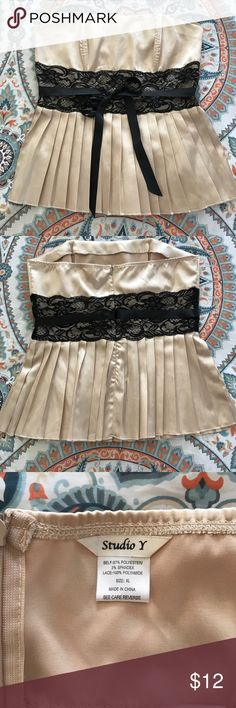 Pleated stretchy light tan camisole with back zip Never worn this gorgeous top has stretch to it so it will fit great! Back zip and boning at the bust with black lace and ribbon tie at the waist. This adorable top will make any outfit special, add black pants or a skirt and heels and you're done! Studio Y Tops Camisoles