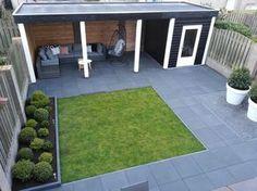 Strakke/moderne kleine achtertuin met donkere bestrating en overkapping/veranda incl. schuurtje