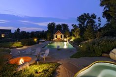 A beautiful pool at dusk with a firepit, spa, Tennessee flagstone pool deck, and custom pool house.