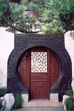 "This door is located in the ""Garden of Peace and Comfort"" or Yu Garden in the old part of Shanghai. It dates from the Ming Dynasty. There are four characters carved above the door."