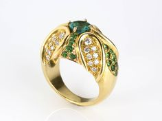 EMERALD TSAVORITE DIAMOND GOLD RING; set with a natural emerald 0.70 ct surrounded by a leafs motif in pave set tsavorite 1.30 ct and brilliant cut diamonds 1.00 ct, G color, VVS clarity. Size US 7. Weight 20.5 gr. Item condition grading: **** good.