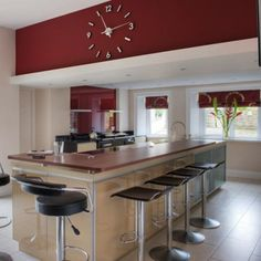 Similar kitchen elements (burgundy walls, stainless steel, black bar stools).
