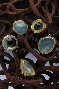 Assorted 18K Gold Rings (clockwise): Aquamarine chunk, Green Tourmaline Shield Ring with White Diamond, Aquamarine Slab Ring with White Diamond, Marquise Shaped Aquamarine Shield Ring with White Diamond, Green Quartz Dome Ring Hughes-Bosca Jewelry | Rings