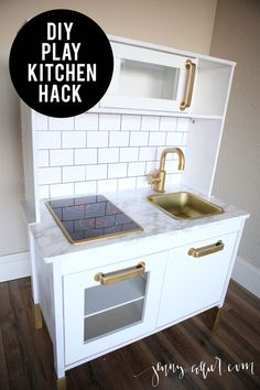 Sharing a tutorial for a chic DIY play kitchen hack featuring white cabinets, a faux marble countertop, and subway tile.