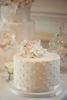 Quilted White Wedding Cake with Flowers. A petite wedding cake decorated with ivory ribbon and tiny pearls was topped with the same delicate sugar flowers.