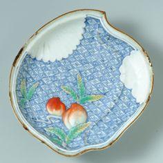 色絵桃文桃型皿/ 桃の形状の中に、桃の色絵が施され、また、桃の色絵の部分が盛り上がっており、複雑な意匠の、鍋島の意匠性をほうふつさせる古伊万里の変形皿である。桃の色絵の周りには染付にて地紋がびっしりと描かれ、縁には銹釉(さびゆう)、裏文様も草花文が染付と色絵の併用にて描かれ、小品ながら手間のかかった優品である。このような変形皿が当時、どのような使われ方をしたのか解らないが、江戸文化が華やいだ頃、賞びられたことは推察できる。