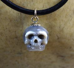 This beautiful high quality grey pearl is 10mm and is hand carved into a full skull. The bail is made of 14k gold. The pearl skull hangs from leather cord, choice of 16 to 20 inches in length. Perfect gift for yourself or a loved one this holiday season. Packaged in a gift box and ships worldwide. *Since the pearl is carved upon order, please allow 7 to 10 business days for your necklace to be completed. The quantity amount is not how many are currently made, it is an option if you are…