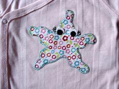 Body rosa con estrella de mar de aplicaciones patchwork de colores.