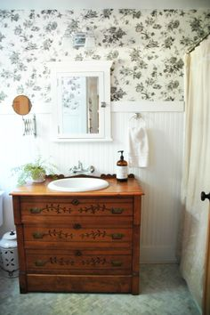 Our new bathroom.  Wallpaper from Lowes.com.  We used my mom's childhood dresser as our sink base.  Floor is honed carrara marble in a herringbone pattern.  White grout which I sorely regret.  ;)