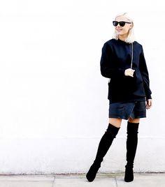 Jessie Bush of We the People wears a black sweatshirt, mini skirt, thigh-high boots, and a crossbody bag