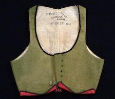 livstycke 1800-30 Grön,blekt vadmal med svarta sammetskanter. Den uppvikta kanten nertill fodrad med rött ylle. Rosa linnefoder.