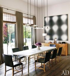 The great room also features vintage pendant lamps from Wyeth, an untitled Wayne Gonzales painting, a Corian-top steel table by Martin Szekely from Galerie Kreo, custom-made chairs by Roman Thomas, and a '50s sideboard by T. H. Robsjohn-Gibbings for Widdicomb.