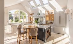 Kitchen island | breakfast bar seating | shaker style kitchen | painted units | vaulted ceiling | velux rooflights | arch window | integrated fridge freezer | range cooker | Victorian property | London life | escape in the city
