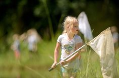 Third-grader Elsie Andre peers into her net to see if she captured a dragonfly as part of Ecology Day Camp at the University of Mississippi Biological Field Station in Abbeville, Mississippi, on June 13, 2012.