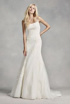 This clean silhouette is both romantic and sexy. Featuring 3D organza flowers applied to tulle and veiled over lace, a spaghetti strap camisole neckline and a plunging back , this wedding dress would