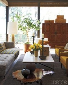 The living room of designer Michael DePerno's renovated midcentury-modern home in Santa Rosa, California, includes vintage pieces such as a Dunbar sofa, a pair of linen-upholstered Danish armchairs, and a Paul McCobb cocktail table; the antique cabinet is Chinese, and the rug is by Tufenkian Artisan Carpets.