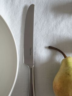Still life with pear and knife on linen table cloth | Design  Hunter