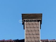 Schornstein mit Verkleidung aus anthrazitfarbenen Schindeln vor blauem Himmel in Oerlinghausen