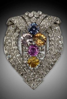An Art Deco platinum, diamond and multi-coloured sapphire brooch, by Cartier, circa 1935. The openwork shield form brooch set with brilliant-cut diamonds, centring multi-coloured sapphires, mounted in platinum.