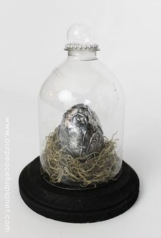 This silver dragons egg is made from a plastic egg, hot glue and silver and black paint. That's it! It looks awesome displayed in my bell jar, which I made from a soda bottle. That tutorial is linked on the post too!