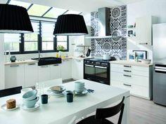 Vue sur l'ensemble de la cuisine noir et blanche avec parquet et plan de travail en bois clair. L'ensemble de ce décor provoque une impression de tranquillité tout en restant très moderne.