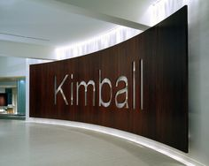 Kimball International - curved wood signage wall Metal Signage, Wayfinding Signage, Signage Design, Curved Wood, Curved Walls, Office Interior Design, Office Interiors, Backlit Signs, Donor Wall