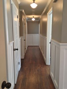 this is really close to what my hallway of doors would look like. Beautiful wainscoting and crown molding for the hallway Wall color: Sherwin Williams Pavestone. Color I used for the whole house. Hallway Wall Colors, Hallway Walls, Hallway Ideas, Wainscoting Hallway, Long Hallway, Wainscoting Nursery, Hallway Inspiration, Upstairs Hallway, Hallway Paint
