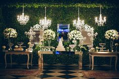 Boxwood hedge backdrop, 4 chandeliers and lots of white flowers