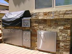 Outdoor stone #kitchen with stainless steel appliances by DH Landscape Design