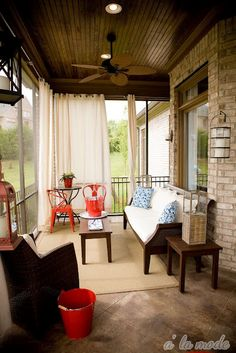 Covered deck with lighting, comfy seating, natural rug, curtains and pops of color.