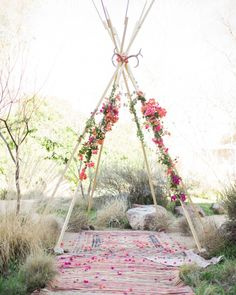 """In planning the non-religious wedding, there were a few elements of Lara's Jewish roots that she wanted to incorporate, the first being getting married under a chuppah. Chad being a designer and builder, wanted to make a unique structure—which the couple dubbed a """"chup-tee"""" (pronounced hooptee)—which he crafted using wood from a local hardware store and antlers from a nearby thrift shop. Fresh bougainvillea finished it off, and vintage rugs were laid out to create a warm and cozy aisle."""