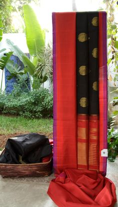This kanchivaram silk is in black with gold zari bhuttas. The border is in violet, red and pink and the pallu is in red with gold zari weave making it a must have for every wardrobe
