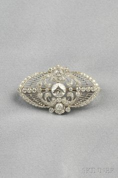 Edwardian Platinum and Diamond Brooch, bezel-set with an old European-cut diamond weighing approx. 0.90 cts., and further set with old European-cut diamonds on knife-edge bars, millegrain accents, lg. 1 1/2 in.