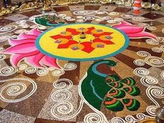 a beautiful rangoli (rice paste) design with peacocks and lotus flowers