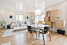 Kaunis ja valoisa olohuoneen ja ruokailutilan yhdistelmä on saanut skandinaavisen ilmeen selkeillä huonekaluilla ja suomalaisilla klassikoilla, kuten Artekin Domus-tuoleilla.