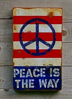 "blue plain painted peace sign over the usa flag white and red stripes and at the bottom its says in white pastel spray paint over a usa flag blue ""PEACE IS THE WAY"""